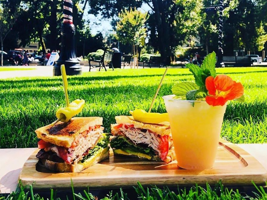 Picture of cocktail and sandwich on a board on grass in Healdsburg Plaza