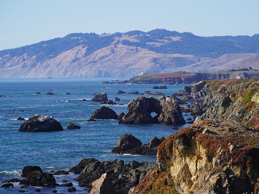 Shot of Highway 1 looking up the Sonoma County coastline, including an arched rock