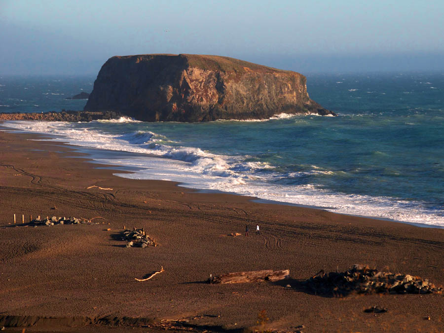 People stroll along the beach at sunset at Goat Rock Beach, Sonoma County