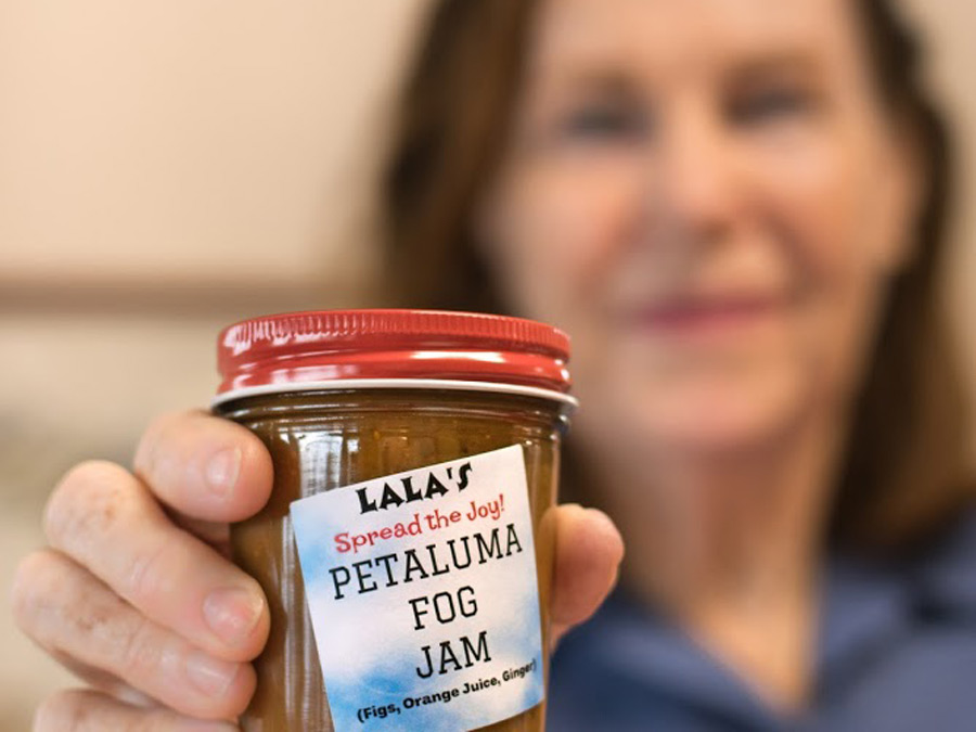 A woman holds a jar of jam that she made