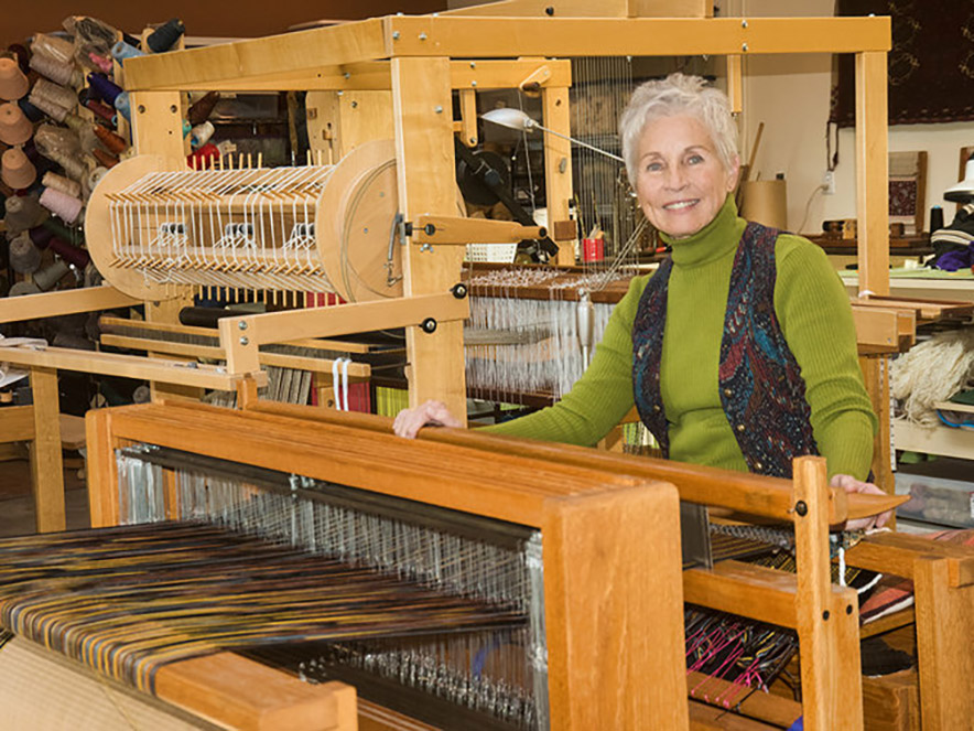 An older artist with close cropped grey hair smiles at their loom in the Artican Shop in BOdega