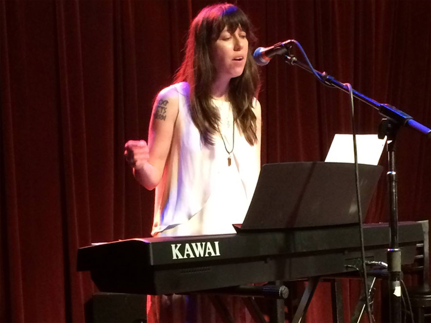 Brittany Aquamarine with keyboard and microphone on a stage