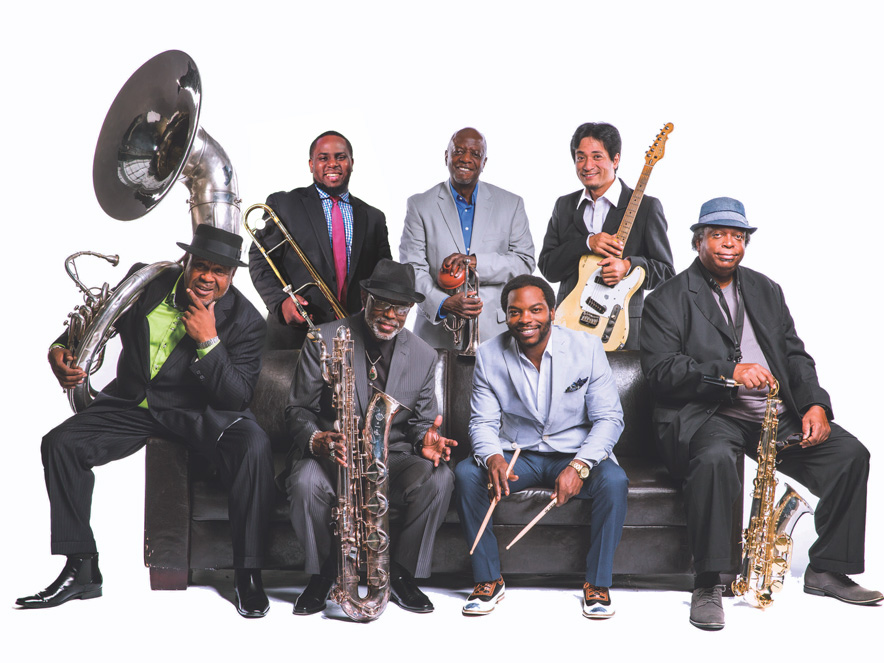 dirty dozen brass band posing with their instruments