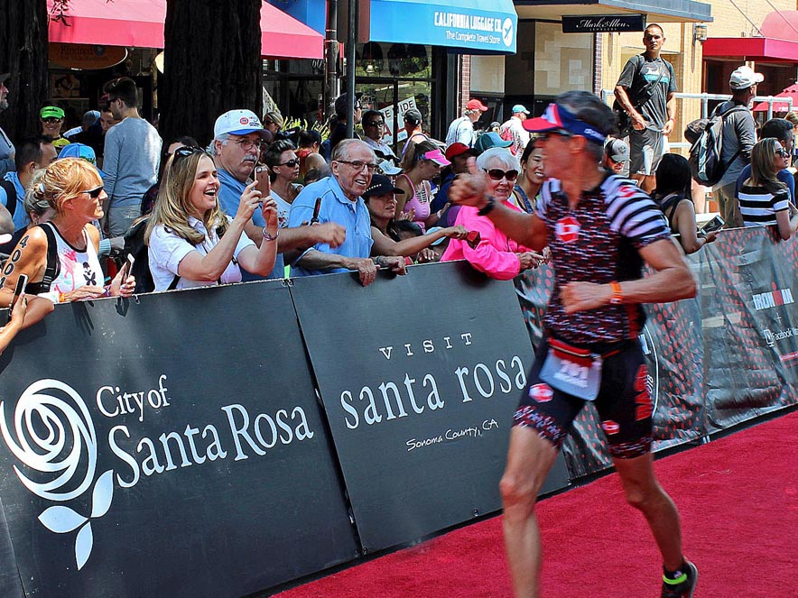 Image of an Ironman competitor running past a crowd.