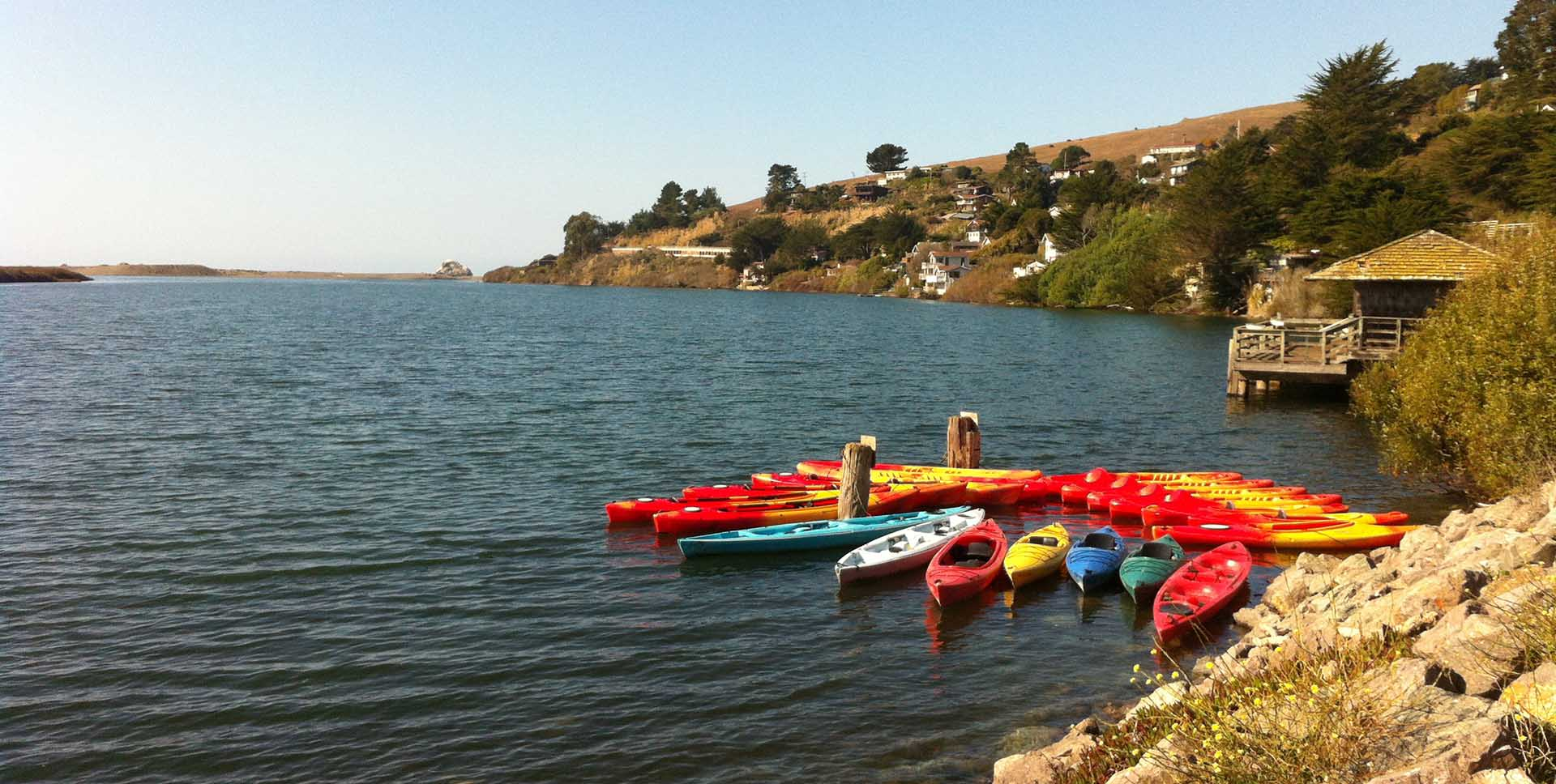 Vibrantly colored kayaks float by the sea village of Jenner, right where the mouth of the Russian River meets the ocean