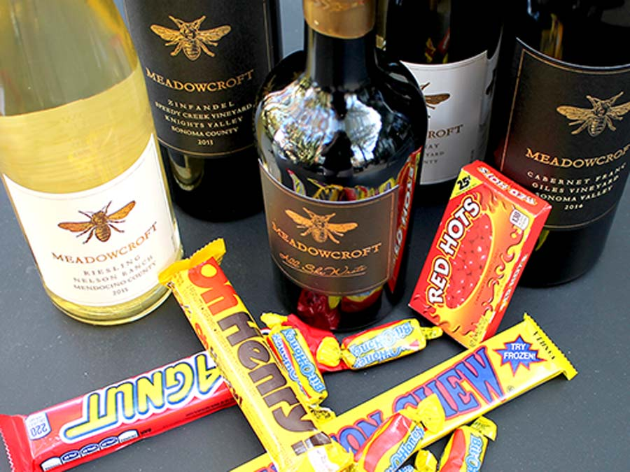 Bottles of red and white wine are lined up on a table withHalloween candy