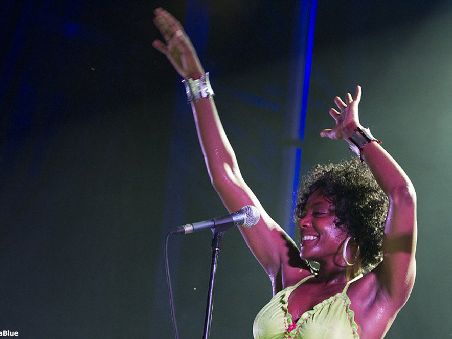 Niki J Crawford performing with her hands in the air in front of a microphone