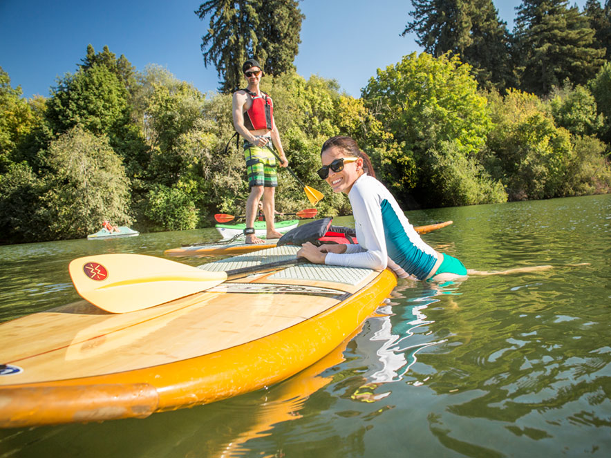 A woman smiles and climbs on a paddleboard while a man follows, riding a paddleboard behind her on the Russian River