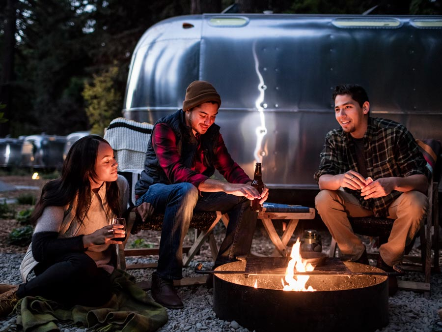 Three people sit around a campfire in front of a luxury Airstream at AutoCamp Russian River in Guerneville