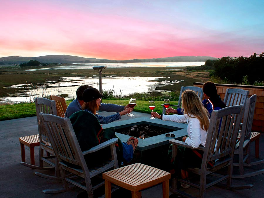 People toast wine glasses by a fire pit overlooking the Pacific Ocean in Sonoma County