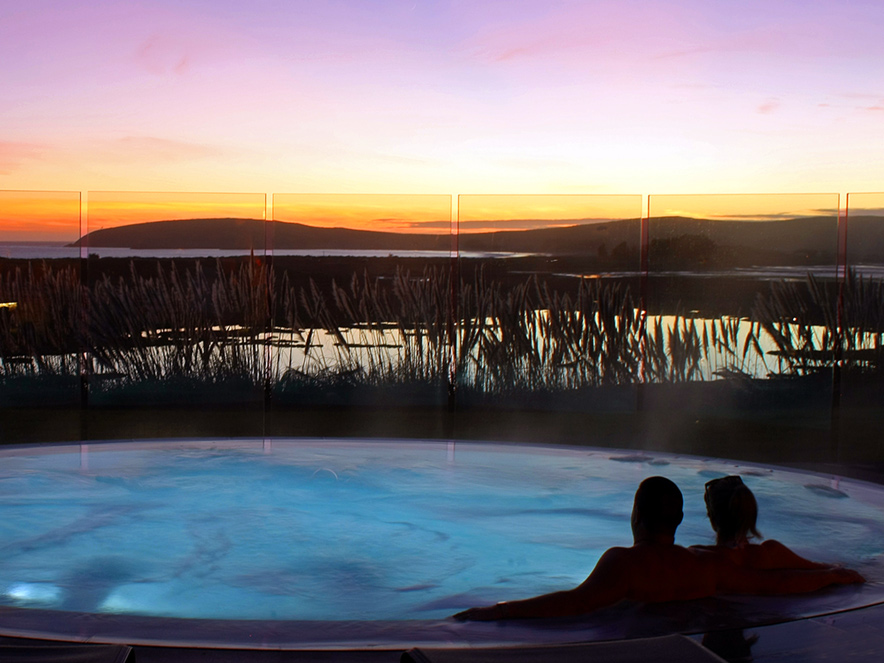 The silhouette of a couple relaxing in a spa under a fiery sunset sky at Bodega Bay Lodge in Sonoma County, California on the coast