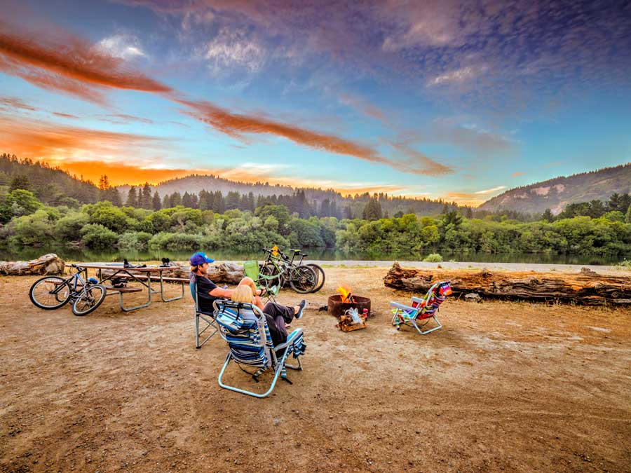 People sit around a fire pit while the sun sets behind them at Casini Ranch Family Campground, Sonoma County