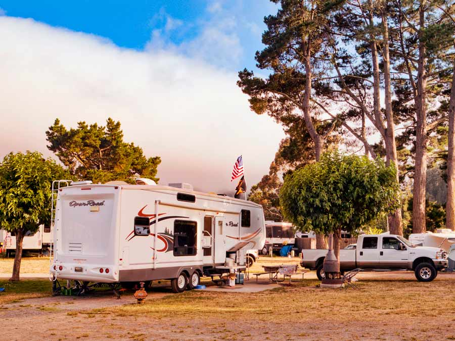 A RV is parked next to trees at Casini Ranch Family Campground, Sonoma County
