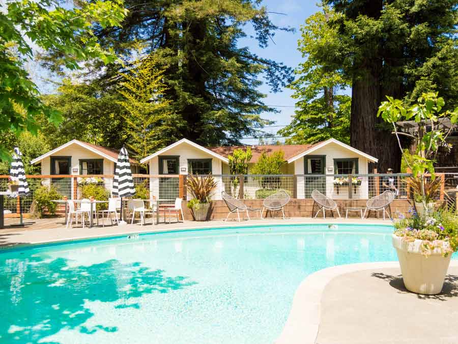 Cute little cottages in a row next to a pool, surrounded by redwoods in Sonoma County