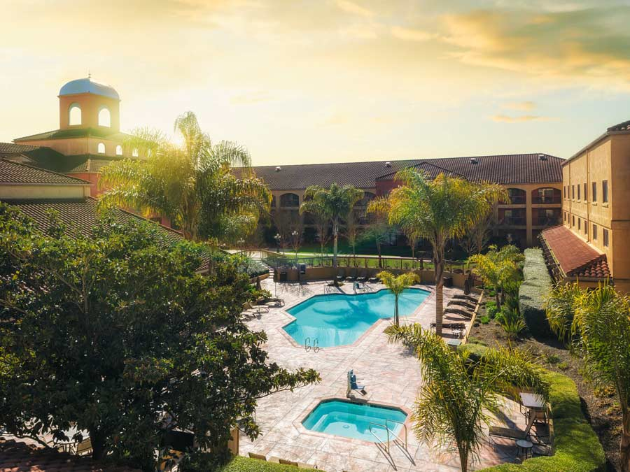 The pool at the Doubletree by Hilton Hotel Sonoma Wine Country is surrounded by palm trees at sunset in Sonoma County