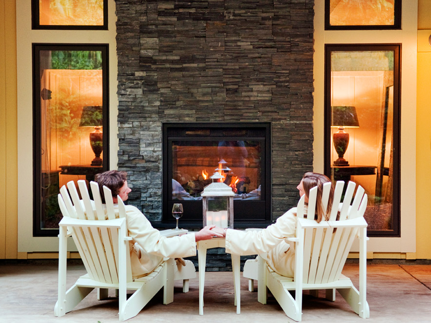 A couple in white bathrobes sit in white deck chairs in front of an outdoor fireplace set in a yellow facade at Farmhouse Inn and Spa in Sonoma County, California