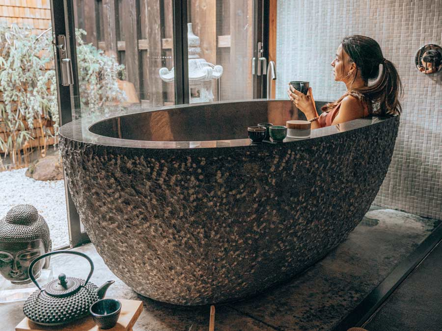 A woman bathes in a giant, round, Japanese-style tub