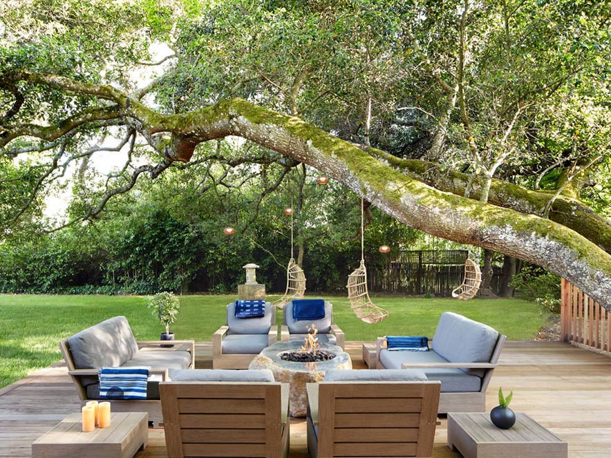 Comfy chairs surround a cozy fire on a patio surrounded by lush greenery at Gaige House + Ryokan in Sonoma County, California