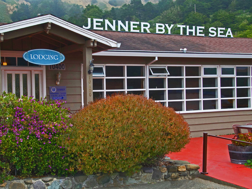 Jenner by the Sea sign hangs over a red overhang at the hotel in Sonoma County