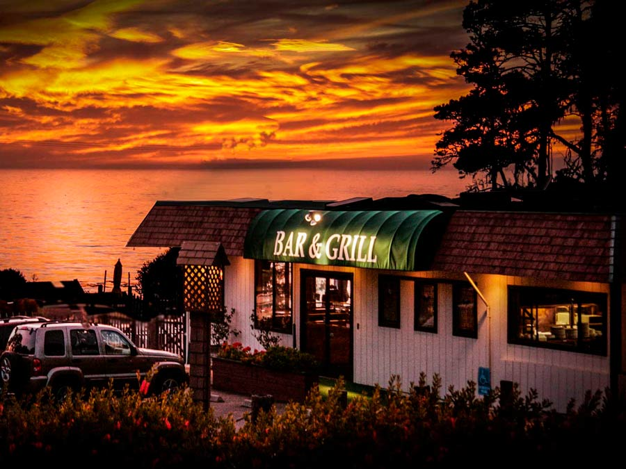 The sun sets along the Sonoma Coast behind the Ocean Cove Lodge Bar & Grill, Jenner