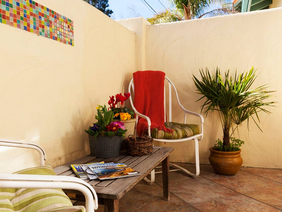 The sunny courtyard has a vintage chair and plants