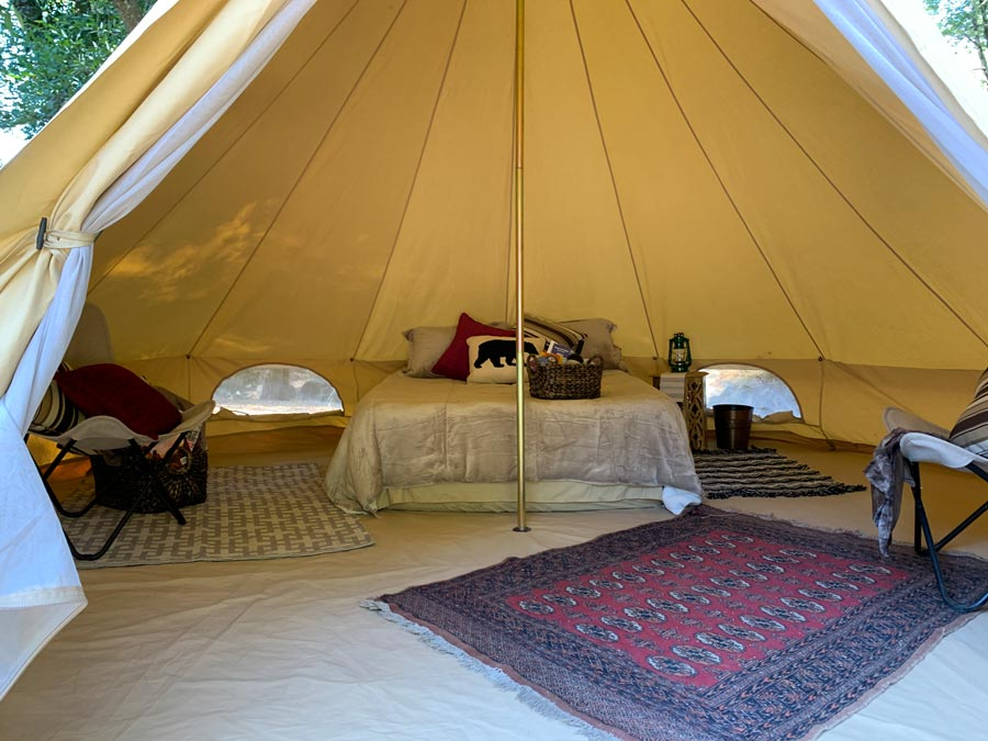 The interior of the luxury tent has rugs and a well-made bed in Sonoma County