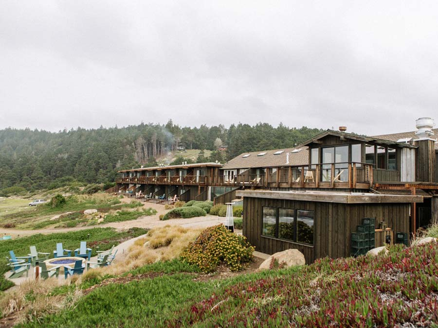A fire pit is surrounded by ice plant in front of the resort along the Sonoma Coast