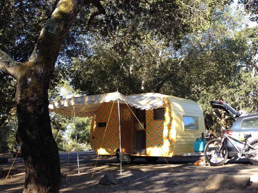 A vintage trailer is set up under the shade of an oak tree at Spring Lake Regional Park, Sonoma County