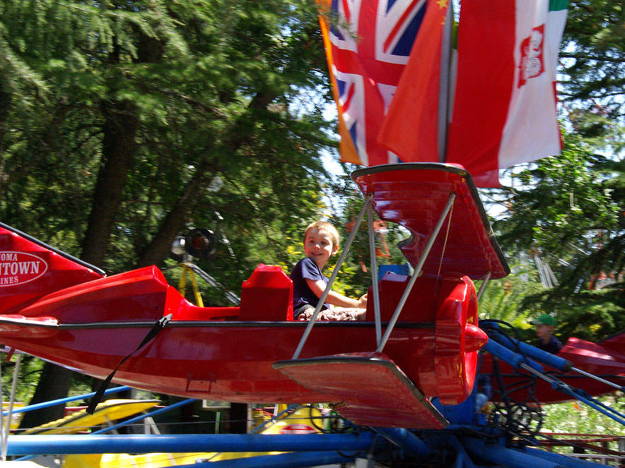 "A little boy has a huge smile on his face as he ""flies"" in an airplane ride at TrainTown in Sonoma"