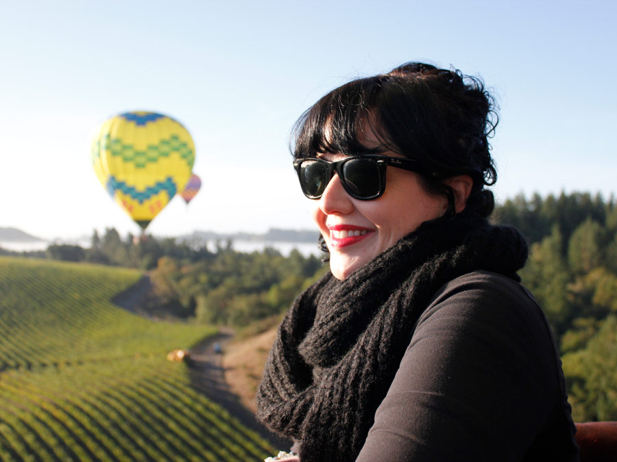 A woman soars over vineyards in a hot air balloon in Sonoma County