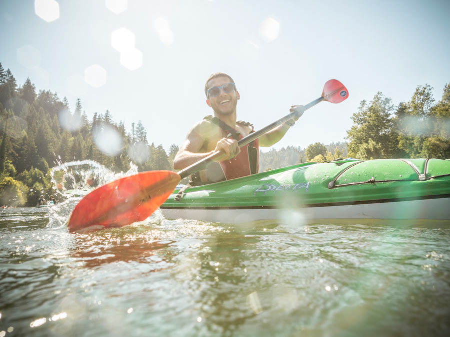 Man wearing sunglasses having a great time kayaking in Sonoma County