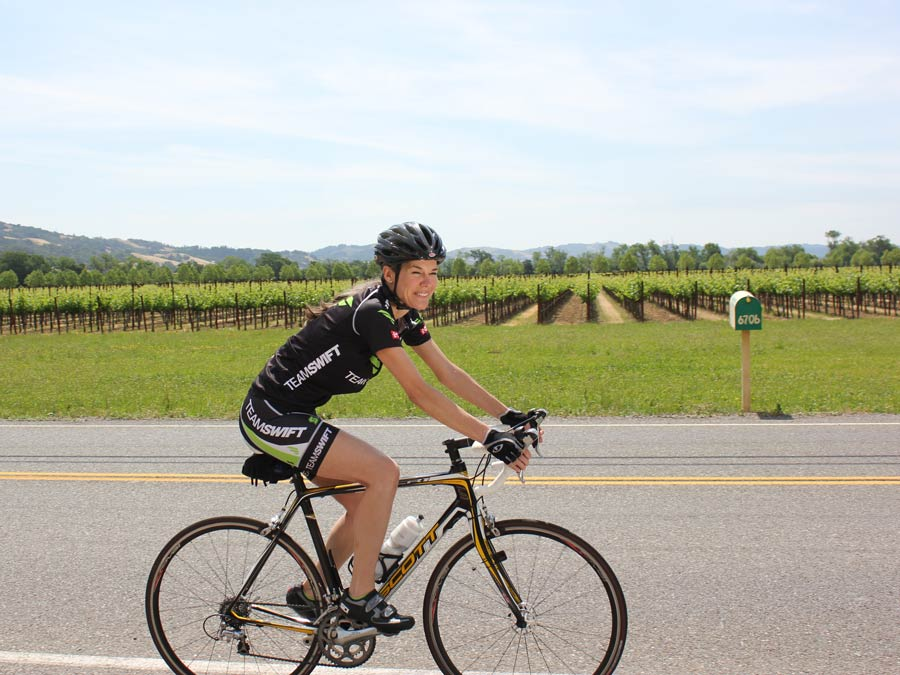 A woman cycles next to vineyards in the summer in Sonoma County