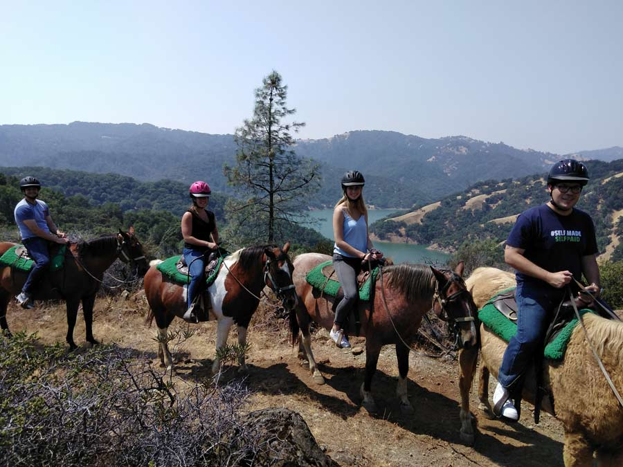 A group rides horses with a view of the lake behind them with The Ranch at Lake Sonoma Horseback Riding, Sonoma County