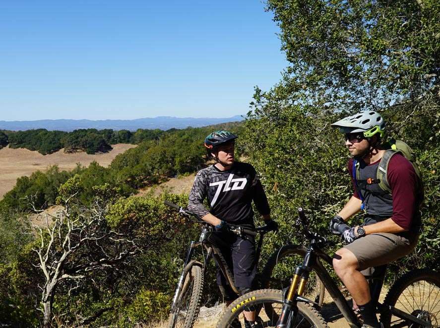 Two men look over the hillside while on mountain bikes at Trione-Annadel State Park, Sonoma County