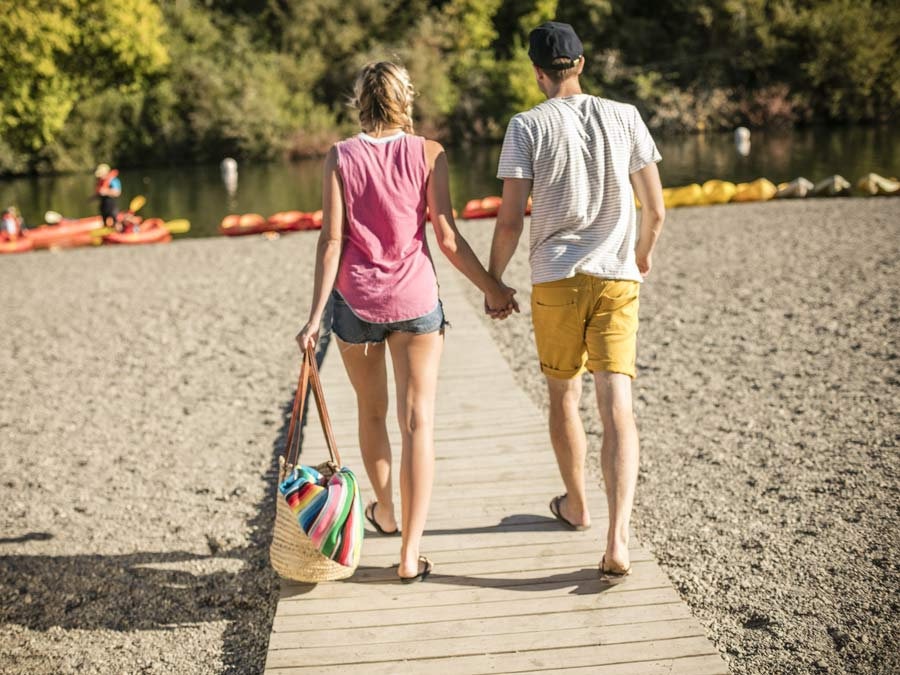 Two people walk toward the Russian River at Johnson's Beach in Sonoma County