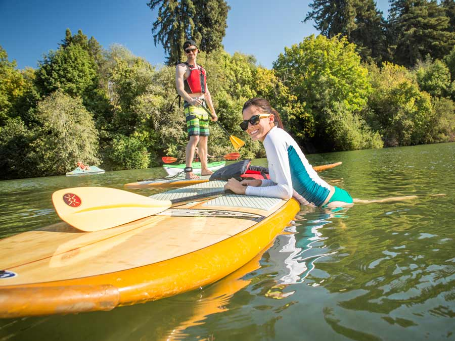 Twee mensen dobberen op de Russian River met peddelbaords in Sonoma County