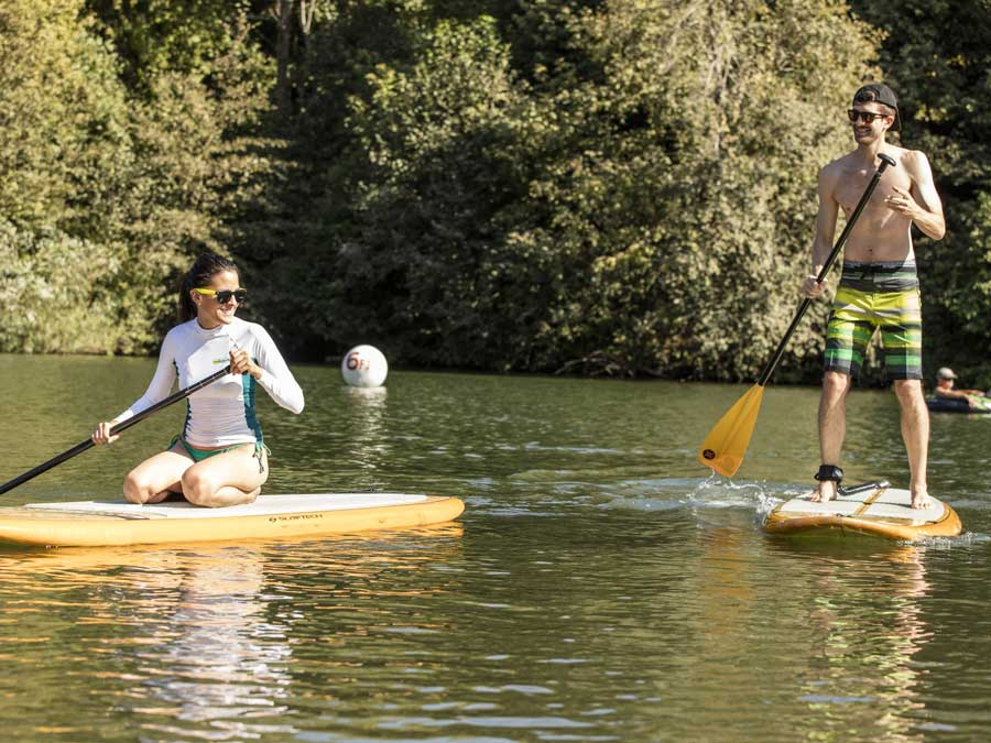Two people paddle board along the Russian River in Sonoma County