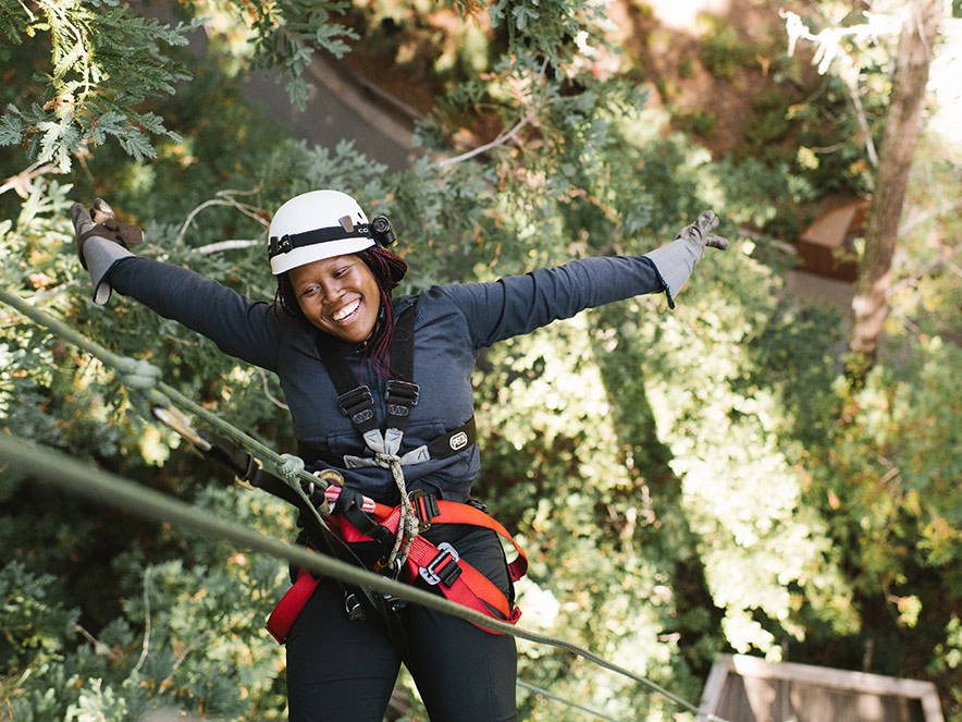 A woman with a huge smile on her face repels out of the redwood trees in Sonoma County
