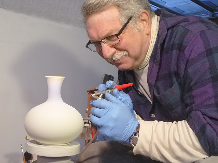 a potter bends over his work of creating a vase at the Artisans Co-Op in Bodega, Sonoma County