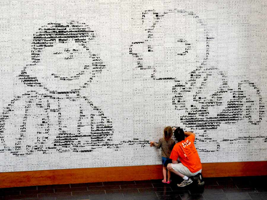 People examine the wall of Peanuts cartoons that make up a larger image at the Charles M. Schulz Museum, Santa Rosa