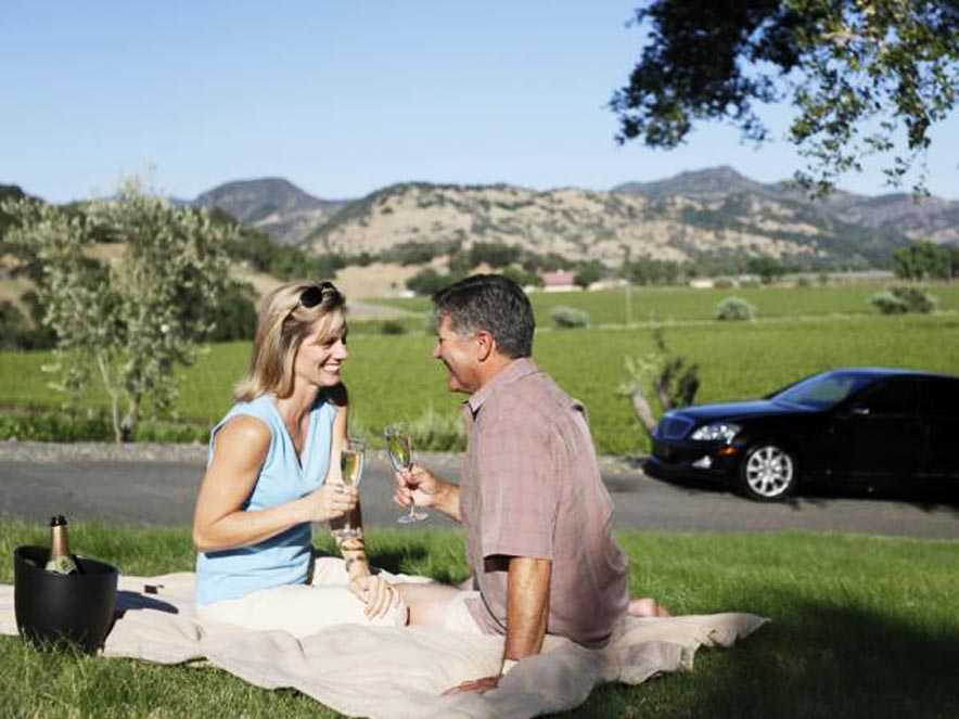 Image of couple in front of car from Beau Wine Tours