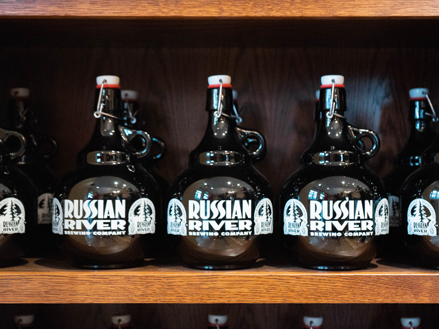 A row of Russian River Brewing growlers sits on a shelf.