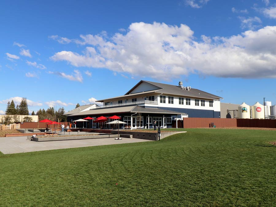 The exterior of the brewery has a big lawn and patio