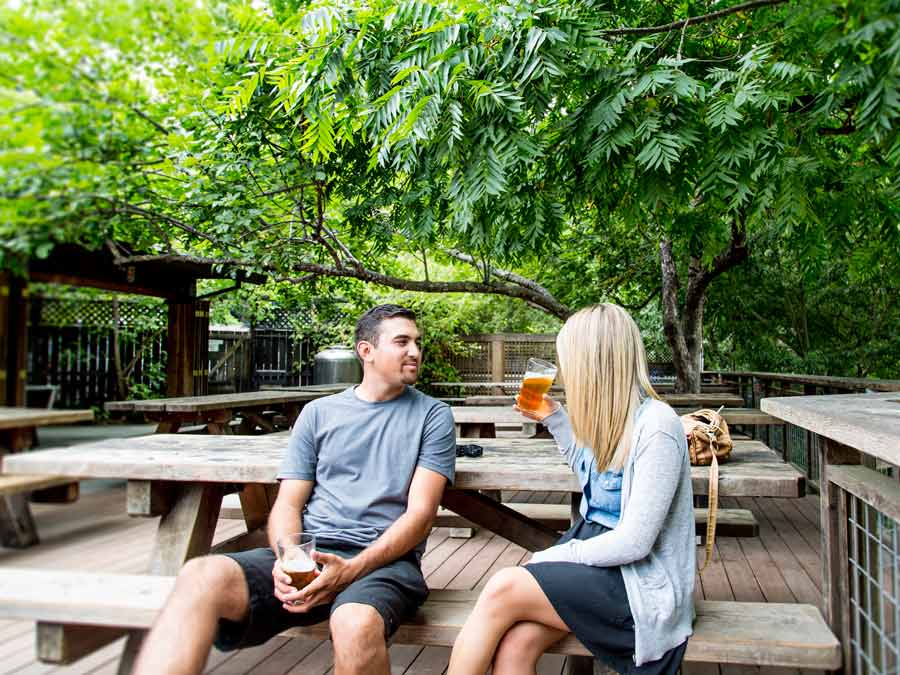 Two people enjoy brews at a picnic table on the deck under the shade of trees in Sonoma County