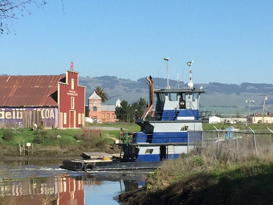 A boat navigates the Petaluma River in front of the David Yearsley River Heritage Center, Sonoma County