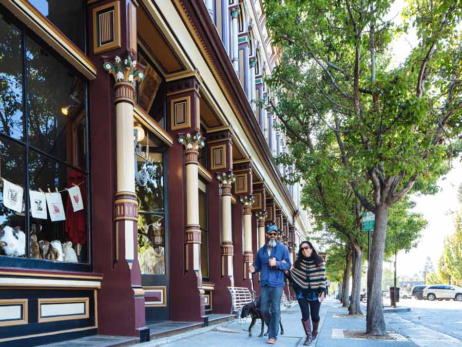Two people walk with their dog next to Victorian buildings in downtown Petaluma, Sonoma County