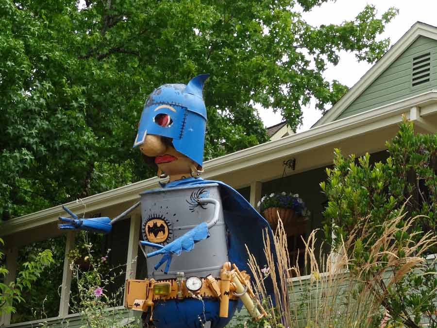 A metal sculpture of Bat Man in front of a house