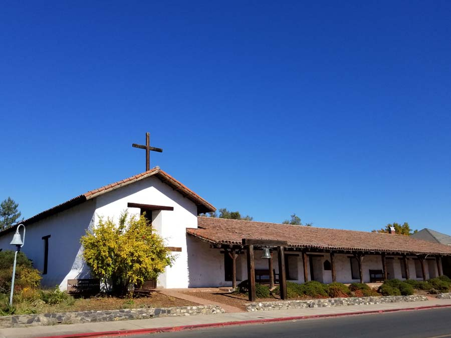 The white stucco mission has a wooden cross on top