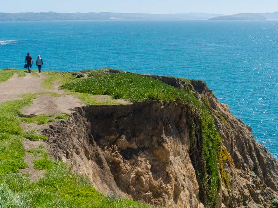 Two people walk along the land's edge at Bodega Head