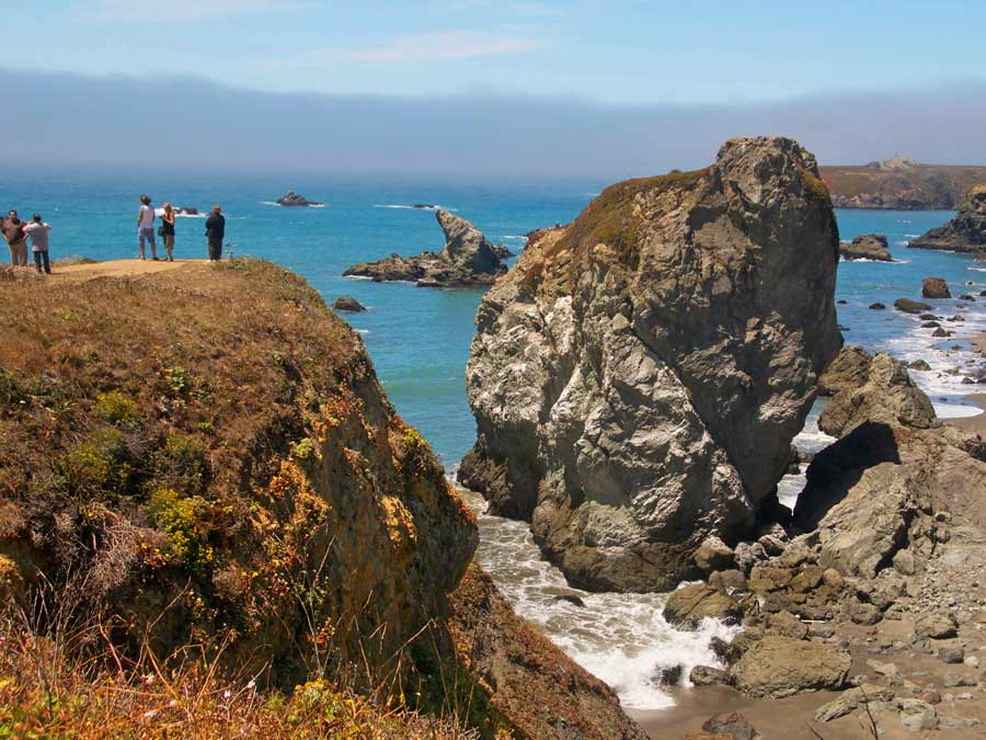 People look at the huge boulder along the Sonoma Coast